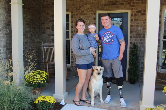 Now a medically retired sergeant, Corey Garmon and his wife Megan and daughter Kyleigh are enjoying the new home made possible by the generous donations of patriots, businesses and organizations. With them is their dog, Bella.