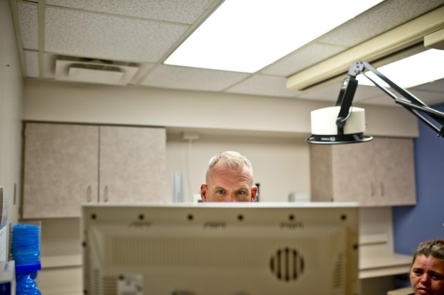 Dr. John Cletus Paumier checks the X-ray of a patient at the Salem Regional Medical Center, Ohio, Sept. 8, 2014. In one morning, Paumier saw approximately 30 different patients, moving from room to room and assessing wounds and the healing progress of each patient quickly, going non-stop for several hours. Paumier is an orthopedic surgeon, officer-in-charge of the Army Reserve Marksmanship Program and command surgeon to the 416th Theater Engineer Command, headquartered in  the command surgeon to the 416th Theater Engineer Command, headquartered in Darien, Ill.
