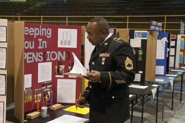 Army Reserve Sgt. 1st Class Darren Mitchell, operations noncommissioned officer, 412th Theater Engineer Command, and Garyville, La., native, judges projects at the Saint Francis Xavier Elementary School science fair in Vicksburg, Miss., Oct. 9. (U.S. Army photo by Staff Sgt. Debralee Best)
