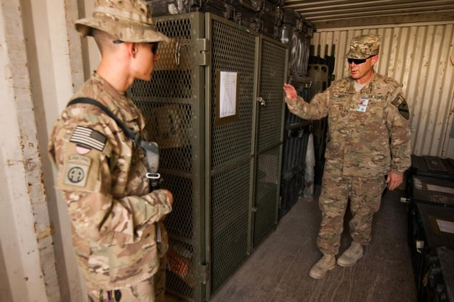 Spc. Joseph Mrsich (left), an infantryman with the 2nd Battalion, 504th Parachute Infantry Regiment, 1st Brigade Combat Team, 82nd Airborne Division, and native of San Dimas, Calif., stands guard in a weapons container while Chief Warrant Officer 5 Norman May conducts an inspection on Kandahar Airfield, Afghanistan, Sept. 27, 2014. May, an Emporia, Kansas native, serves as senior maintenance technician for Regional Command-South and 1st Cavalry Division, conducting inspections for all of coalition forces on KAF and ensuring they are following their established downgrade timelines in preparation for the Resolute Support Mission, which begins Jan. 1.