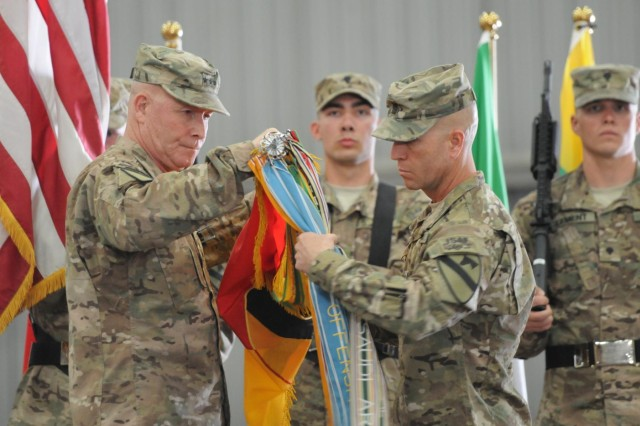 Maj. Gen. Michael Bills, commanding general of 1st Cavalry Division and Regional Command-South, and Command Sgt. Maj. Andrew Barteky, the 1st Cav. Div. and RC-South command sergeant major, cased the 1st Cav.'s colors during a ceremony on Kandahar Airfield, Afghanistan, to commemorate the transition of RC-South to the new Train Advise and Assist Command-South, Oct. 14, 2014. Both the 1st Cav. Div. colors and the colors of Commander, Kandahar Airfield were cased, signifying the beginning of the TAAC-South mission. (U.S. Army photo by Staff Sgt. John Etheridge)