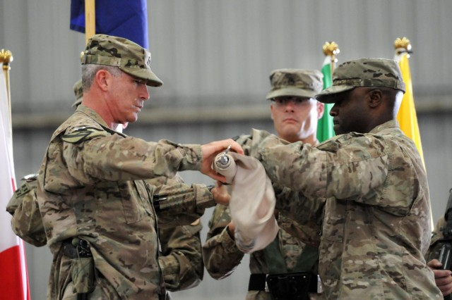 Air Force Brig. Gen. Michael Fantini, commanding general of Kandahar Airfield, and Command Master Chief Eric Johnson, senior enlisted adviser of COMKAF, case the COMKAF colors during a ceremony on Kandahar Airfield, Afghanistan, to commemorate the transition of RC-South to the new Train Advise and Assist Command-South, Oct. 14, 2014. Both the 1st Cav. Div. colors and the colors of COMKAF were cased, signifying the beginning of the TAAC-South mission. (U.S. Army photo by Staff Sgt. John Etheridge)