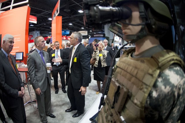 Under Secretary of the Army Brad R. Carson (in gray suit) inspects new advances in technology to help the war fighter at the AUSA annual convention and exposition, Oct. 14, 2014, at the Walter E. Washington Convention Center, Washington, D.C.  AUSA is a private, non-profit educational organization that supports America's Army - Active, National Guard, Reserve, Civilians, Retirees, Government Civilians, Wounded Warriors, Veterans, and family members. (U.S. Army photo by Staff Sgt. Bernardo Fuller/Released)