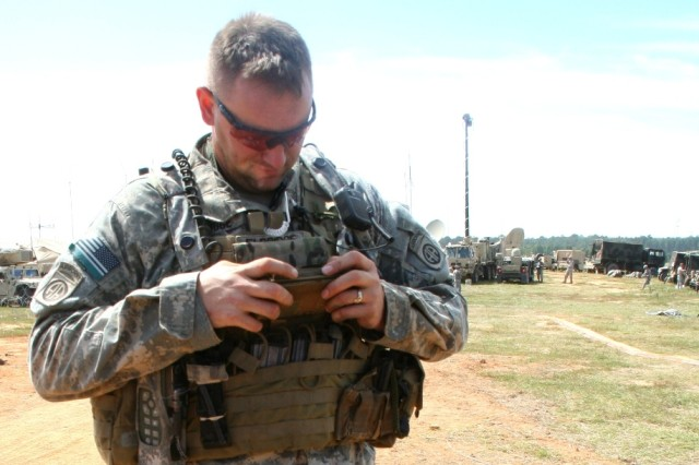 A Soldier from the 2nd Brigade Combat Team/82nd Airborne Division's, uses his Capability Set 14 software defined Rifleman Radio and handheld smartphone-like device, referred to as Nett Warrior, at the units' Joint Readiness Training Center (JRTC) rotation at Fort Polk, La., on September 22, 2014  (U.S. Army photo by Amy Walker, PEO C3T).