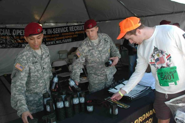 Special Operations Recruiting Battalion's Sgt. 1st Class Rolando Sarabia and Sgt. 1st Class Daniel Hollis talk up the crowd and distrIbute SWAG at the SORB booth in the Hooah Zone Oct. 12 at the Pentagon.