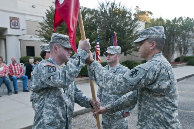 U.S. Army Reserve Capt. Nicholas Oates (left), outgoing commander, Headquarters and Headquarters Company, 412th Theater Engineer Command, accepts the unit guidon from HHC 1st Sgt. Richard Broussard, during the HHC change of command ceremony in Vicksburg, Miss., Oct. 19. (U.S. Army photo by Staff Sgt. Roger Ashley)