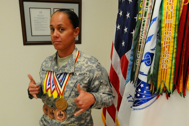 FORT SHAFTER, Hawaii - Breast cancer survivor, native Hawaiian, Soldier, mother and athlete Sgt. Kawaiola Nahale, a U.S. Army Reserve budget analyst with the 311th Signal Command, poses with the seven medals she won in the Invictus Games and Warrior Games. One year and three surgeries after breast cancer diagnosis, Nahale represented the U.S. Army at the international games in London and national games in Colorado and brought home these seven medals. (Photo by Sgt. 1st Class Crista Mary Mack, 311th Signal Command)