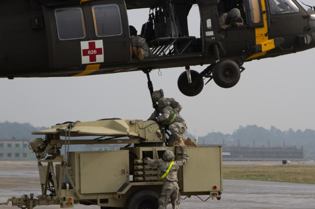 Sgt.  Joseph W. Hatcher, a cable system installer and maintainer, A Co. 304th Expeditionary Signal Battalion, 1st Signal Brigade attaches the satellite equipment to a Black Hawk on taxiway D, Camp Humphreys, South Korea on Oct. 16 during sling load training.