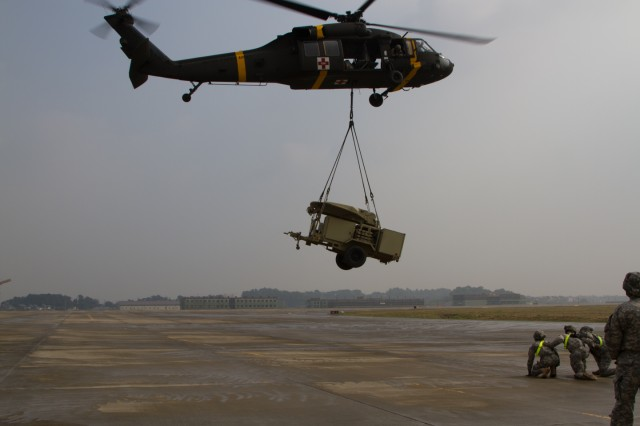 Pilots of a U.S. Army Black Hawk take off with the satellite equipment sling loaded at taxiway D, Camp Humphreys, South Korea on Oct. 16 during sling load training conducted by 304th Expeditionary Signal Battalion.