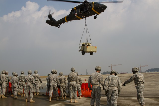 Soldiers of the 304th Expeditionary Signal Battalion observe the flight as pilots of a U.S Army Black Hawk land the satellite equipment on the air strip at taxiway D, Camp Humphreys, South Korea on Oct. 16 during sling load training.