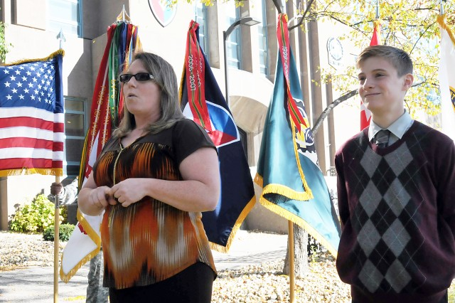 Kelly Mulder speaks during a ceremony Oct. 22 upon being recognized as the 2013 Army Sustainment Command LAR of the Year. Flanking her is son Nathaniel. (Photo by Jon Micheal Connor, ASC Public Affairs)