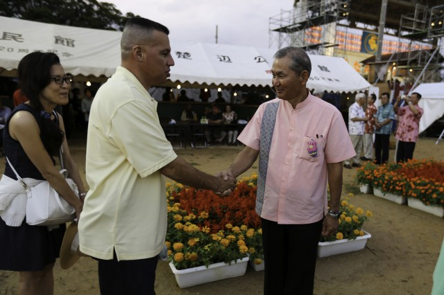 Lieutenant Col. Eric A. Martinez, U.S. Army Garrison - Okinawa commander, greets an event organizer Oct. 26 during the 2014 Yomitan Village Festival on Okinawa, Japan.