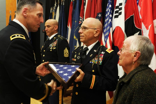Maj. Gen. Thomas S. Vandal, commanding general of the 2nd Infantry Division, presents Chief Warrant Officer 5 Ralph E. Rigby an encased flag, as a token of appreciation for his 42 years of dedicated service in the U.S. Army, during his retirement ceremony on Camp Red Cloud, South Korea, Oct. 28, 2014. Rigby is the last continuously serving draftee in the U.S. Army, and is retiring after 42 years of service.