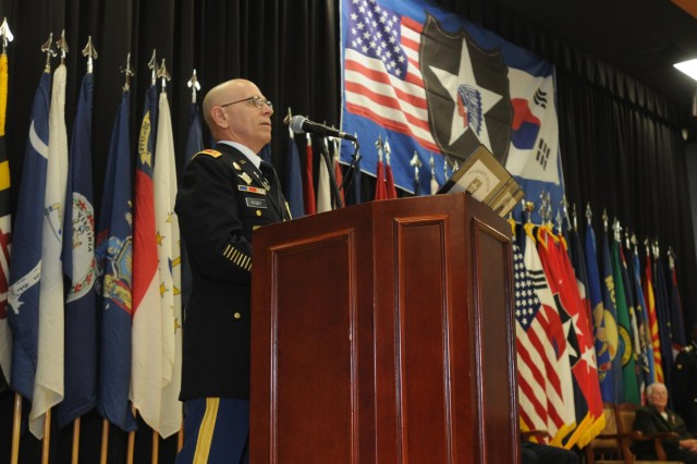 Chief Warrant Officer 5 Ralph E. Rigby speaks to the audience, during a retirement ceremony held in his honor, on Camp Red Cloud, South Korea, Oct. 28, 2014. Rigby is retiring after 42 years of military service, and is the last continuously serving draftee on active duty.