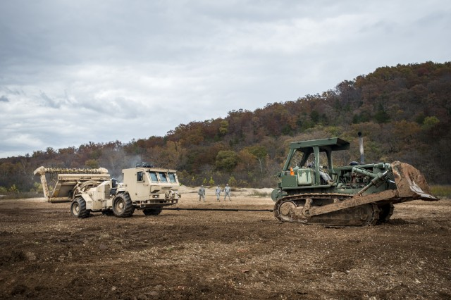 An Army bulldozer tows the M1271 Mine Clearing Vehicle during the extraction and recovery portion of a week-long team-oriented course held at Fort Leonard Wood, Mo., Oct. 30, 2014, put together for the 364th Engineer Platoon (Area Clearance). The M1271, also known as the Medium Flail, is designed to clear through a minefield using a rotating arm with chains and hammers that strike into the ground to destroy or detonate mines.