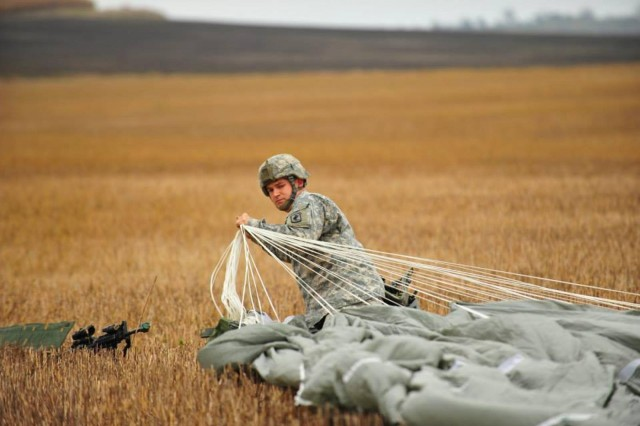 A paratrooper from 1st Squadron, 91st Cavalry Regiment, 173rd Airborne Brigade, gathers his parachute during an emergency deployment readiness exercise at Bogata, Romania, Oct. 21, 2014.
