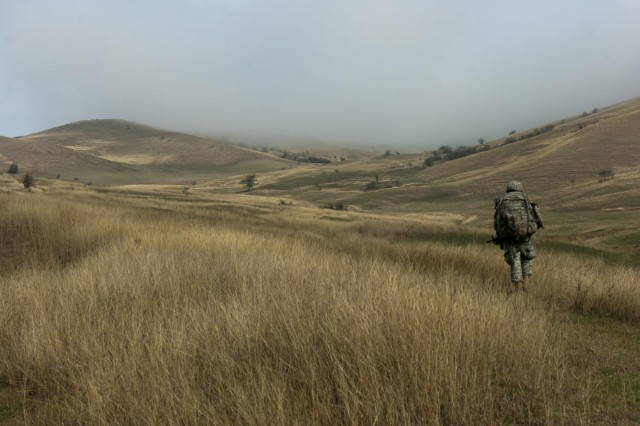A paratrooper from the 1st Squadron, 91st Cavalry Regiment, 173rd Airborne Brigade, ascends a mountain during an emergency deployment readiness exercise in Calarasi, Transylvania,