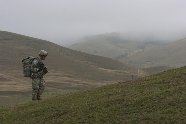 A paratrooper from the 1st Squadron, 91st Cavalry Regiment, 173rd Airborne Brigade, ascends a mountain during an emergency deployment readiness exercise in Calarasi, Transylvania, Romania, Oct. 22, 2014.