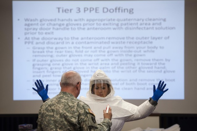 Lt. Col. Neal Woollen, United States Army Medical Research Institute of Infectious Diseases director of bio security, demonstrates how to don and doff personal protective equipment with the help of Pfc. Kaiya Capuchino, USAMRIID combat medic, during hazardous material training Oct. 30, 2014, at Tripler Army Medical Center, Hawaii.  Members of USAMRIID conducted the class to help ensure Service members and civilians are better prepared to react to and defend themselves against infectious diseases at Tripler Army Medical Center.