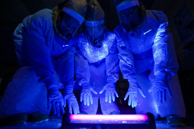 A black fluorescent light shows where simulated bodily fluid containing a mock Ebola virus landed on a care team's personal protective equipment, during a training exercise at Madigan Army Medical Center's Andersen Simulation Center, Nov. 6, 2014, at Joint Base Lewis-McChord, Wash. Madigan has special care teams training to care for potential Ebola patients with advanced patient simulators in intensive care unit environments. The Ebola virus is transmitted through bodily fluids of infected patients.