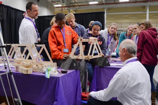 Army chemical engineer Robert Snyder, left, leads an enthused group of STEM Expo participants in a bridge building exercise. Snyder works for the U.S. Army Chemical Materials Activity.