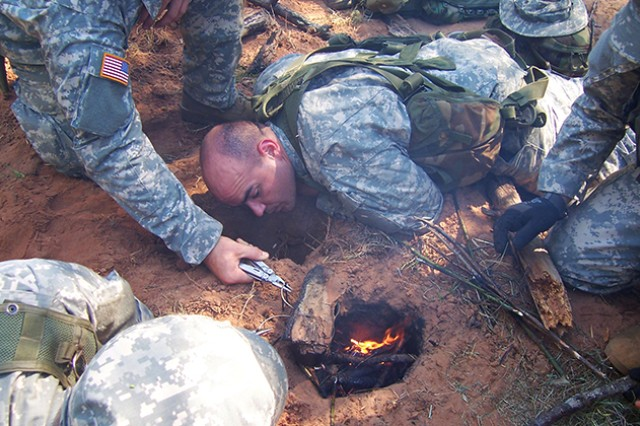 SERE students apply what they learned to construct a Dakota hole to provide fire covertly so as not to attract enemy forces.