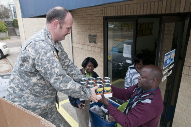 U.S. Army Reserve Staff Sgt. David Putnum, supply sergeant, 412th Theater Engineer Command, hands canned and dry goods to Cedrick Douglas, logistics management specialist, 412th TEC,  Nov. 25 following the 412th TEC food drive in Vicksburg, Miss. The 412th TEC collected approximately 2,000 items and donated them to the United Way of West Central Mississippi. (U.S. Army photo by Staff Sgt. Debralee Best)