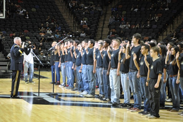 Brig. Gen. Jeffrey Gabbert recites the oath of enlistment to 60 future Soldiers as part of pregame activities at a San Antonio Spurs game Nov. 8 in San Antonio. Gabbert is the commanding general of the Mission and Installation Contracting Command at Joint Base San Antonio-Fort Sam Houston, Texas. (U.S. Army photo by Ben Gonzales)
