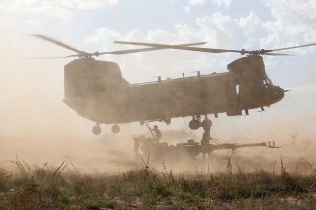 Artillery crew members assigned to Bravo Battery, 4th Battalion, 27th Field Artillery Regiment, Division Artillery, 1st Armored Division, sling load an M777A2 Howitzer beneath a CH-47 Chinook helicopter during air assault operations training at Oro Grande Range, New Mexico.  This training was conducted during Network Integration Evaluation 15.1, under 2nd Brigade Combat Team, 1st Armored Division, Fort Bliss, Texas.
