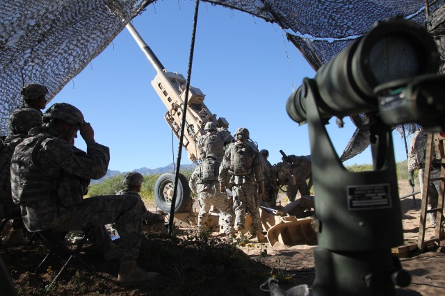 Artillery cannon crew members assigned to Bravo Battery, 4th Battalion, 27th Field Artillery Regiment, Division Artillery, 1st Armored Division, prepare to high angle fire a 155mm high explosive round from the M777A2 Howitzer, while maneuvering throughout the Doña Ana Range Complex, New Mexico. This training took place during Network Integration Evaluation 15.1, throughout Fort Bliss, Texas, training areas.