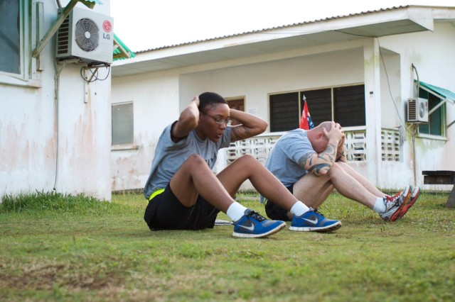 Second Lt. Shenelle Gabriel, left, platoon leader, and Sgt. 1st Class Anthony Harris, platoon sergeant, assigned to Joint Forces Command-United Assistance, conduct physical readiness training in an area treated with insect repellent at Barclay Training Center, Monrovia, Liberia, Dec. 3, 2014. Precautionary measures like spraying insect repellent and eliminating standing pools of water are put in place to prevent breeding grounds for mosquitoes, which carry malaria. Both Soldiers are deployed in support of Operation United Assistance, a Department of Defense operation in Liberia to provide logistics, training and engineering support to U.S. Agency for International Development-led efforts to contain the Ebola virus outbreak in western Africa.