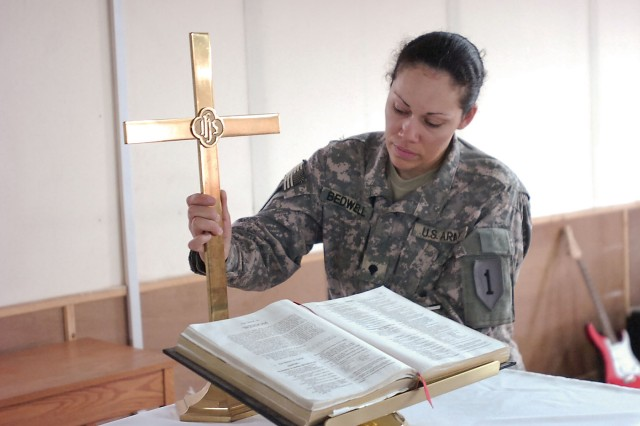 "CONTINGENCY OPERATING SITE WARRIOR, Iraq -- Spc. Faith Bedwell, a chaplain assistant assigned to Company C, 101st Brigade Support Battalion, 1st Advise and Assist Task Force, 1st Infantry Division, prepares the pulpit at Freedom Chapel, Contingency Operating Site Warrior, May 19, 2011, during her daily upkeep of the chapel. ""I don't see myself as a great person, but I believe, spiritually speaking, we're all supposed to help people in need,"" said the Chatom, Ala., native. ""Love your neighbor as yourself, take care of those who need help, hug someone who's crying, and laugh with those who laugh."