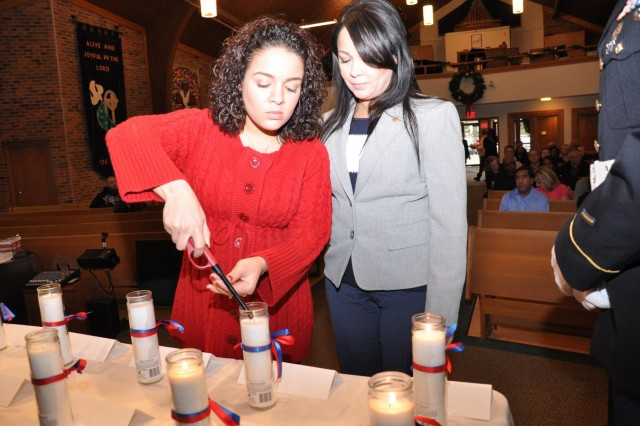 Sgt. 1st Class Hector J. Cruz's wife, Sandra Cruz, and daughter, Rotceh Cruz-Nolan, light a candle in honor and memory at a remembrance ceremony at St. John Lutheran Church in Darien, Ill., Dec. 6 as part of the 416th Theater Engineer Command Family Programs.