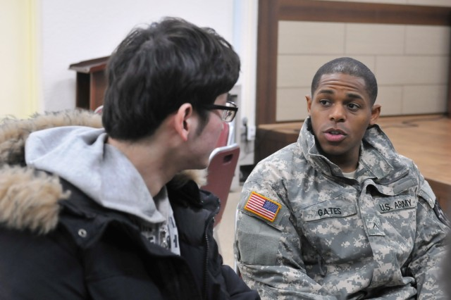 DONGDUCHEON, South Korea -- Pvt. Vincent Gates, a native of Augusta, Ga., and a health care specialist assigned to Headquarters and Headquarters Battery, 210th Field Artillery Brigade, talks to a local Dongducheon citizen during an English Village class December 4, 2014 in Dongducheon, South Korea.
