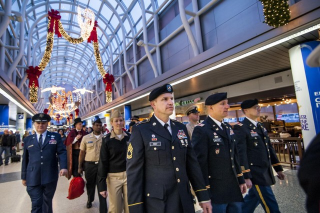 A parade of Army Reserve Soldiers from the 416th Theater Engineer Command, headquartered in Darien, Ill., as well Chicago Police, carolers and service members from the U.S. Marines, Air Force and Navy around the greater Chicago area, marches through the O'Hare International Airport to kick off the celebration for the Snowball Express farewell ceremony, Dec. 11. Snowball Express is a nonprofit organization sponsored by American Airlines that organizes an all-expenses-paid trip for children and spouses who have lost a fallen military hero to offer them support, activities, healing and positive memories during the December holiday season. (U.S. Army photo by Sgt. 1st Class Michel Sauret)