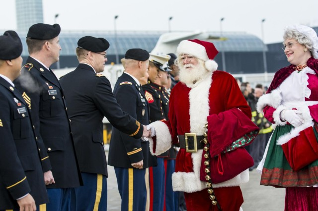 Mr. and Mrs. Santa Claus shake hands with military service members during a Snowball Express farewell ceremony at the Chicago O'Hare International Airport, Dec. 11. Snowball Express is a nonprofit organization sponsored by American Airlines that organizes an all-expenses-paid trip for children and spouses who have lost a fallen military hero to offer them support, activities, healing and positive memories during the December holiday season. (U.S. Army photo by Sgt. 1st Class Michel Sauret)