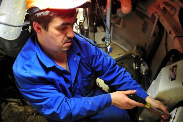 Schwebel Volodymyr, a maintenance specialist with the 21st Theater Sustainment Command's Theater Logistics Support Center-Europe and a native of Slavyansk, Ukraine, removes components from inside an M1A2 Abrams tank in preparation for cleaning and retrograde maintenance Dec. 11 on Kaiserslautern Army Depot. The tank belongs to 1st Brigade Combat Team, 1st Cavalry Division and will return to the U.S. after use in the Baltic region of Europe during Operation Atlantic Resolve.