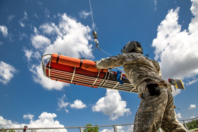 A U.S. Army Aeromedical Research Laboratory medic participates in a mock rescue mission to test an anti-rotational device that could reduce or nullify the spinning of a load when lifted by a hovering helicopter.