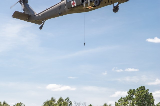 A U.S. Army Aeromedical Research Laboratory medic prepares a rescue basket to be hoisted to an HH-60M during testing of an anti-rotational device.