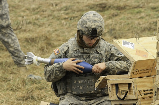 "Pvt. Shane Sanders, Headquarters and Headquarters Company, 2nd Battalion, 14th Infantry Regiment ""Golden Dragons,"" 2nd Brigade Combat Team, sets the fuse function on a 120 mm practice mortar round during their semiannual Mortar External Evaluation Program Dec. 1-17 on Fort Drum."