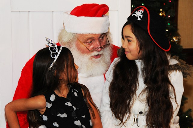 Sisters Anya and Layla Ferrer, military family members, tell Santa what they want under their Christmas tree this year.