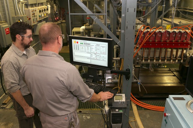 Mechanical engineer Chris Humiston (left) and engineering technician Joe Carter, both with the U.S. Army Armament Research, Development and Engineering Center, monitor the operation of the electrochemical cell at Watervliet Arsenal, New York. An in-house designed closed loop system controls and monitors the operation of the pumps, voltage and actuation of the manufacturing cell.