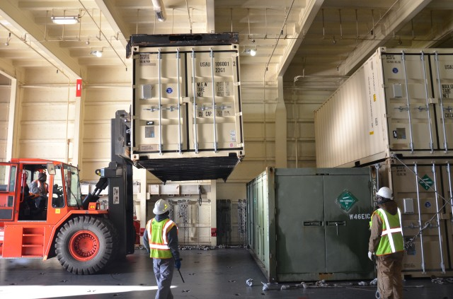 Shipping containers are loaded into the cargo hold of USNS Watkins.