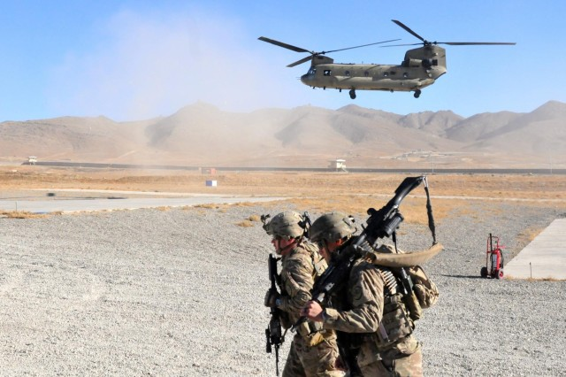 """Two 3rd Cavalry Regiment soldiers providing security for the Train, Advise, Assist Command - East expeditionary advisory package to Forward Operating Base Thunder prepare to board a CH-47 Chinook helicopter at the conclusion of the advising trip Dec. 10, 2014. The soldiers conducted security at a """"cold base"""" or base unoccupied by U.S. coalition forces Dec. 8-10, 2014, so advisers could safely discuss issues with their Afghan counterparts. (U.S. Army photo by Maj. Vance Trenkel) (Released)"""