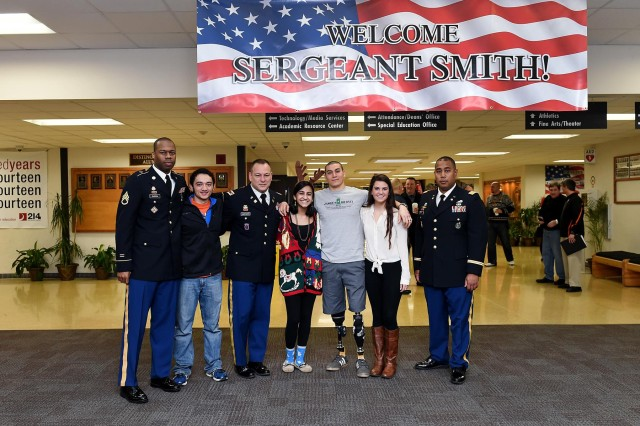 From left to right: Staff Sgt. Terence Barron, 85th Support Command; Owen Connor, John Hersey High School senior; Lt. Col. Craig Lanigan, 85th Support Command; Mili Pandya, JHHS senior; retired Army sergeant Jason Smith, wounded warrior; Carolyn Niersbach, JHHS senior; and Maj. Lawrence Reid, 85th Support Command pause for a photo during a welcome at John Hersey High School, Dec. 19. Smith was invited to JHHS to be honored and presented with a ceremonial check representing the $18,000 that was raised to build a home for him and his family.