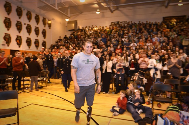 Jason Smith, wounded warrior, is introduced to an assembly of 2,000 students and staff members from John Hersey High School during a welcome at John Hersey High School, Dec. 19. Smith was invited to JHHS to be honored and presented with a ceremonial check representing the $18,000 that was raised to build a home for him and his family.