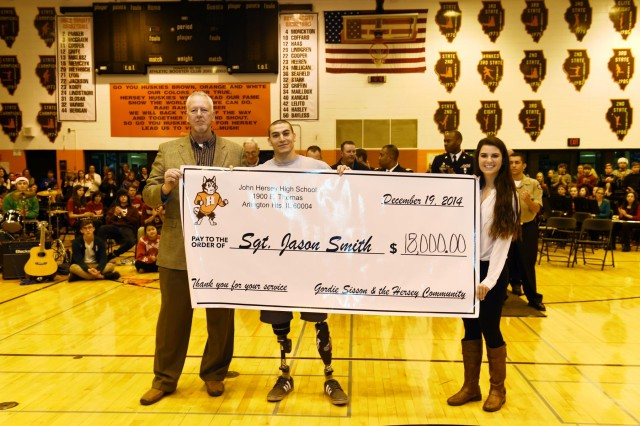 Retired Army Sgt. Jason Smith, wounded warrior; receives a ceremonial check representing $18,000 that was raised to build a home for him and his family, Dec. 19. Smith was invited to JHHS to be honored in front of 2,000 students and staff members from John Hersey High School.