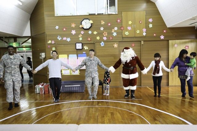 Soldiers from U.S. Army Garrison Okinawa's Better Opportunities for Single Soldiers program dance with the children of the Tsukushi-En special needs school in Okinawa City Dec. 17 during a visit by Santa.