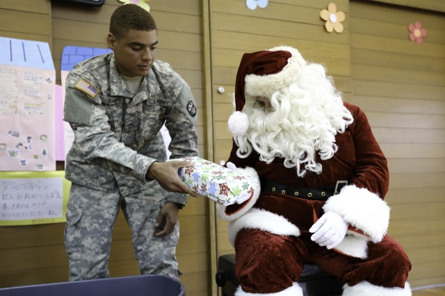 A Soldier from U.S. Army Garrison Okinawa's Better Opportunities for Single Soldiers program hands Santa a gift during a visit to the Tsukushi-En special needs school in Okinawa City Dec. 17.