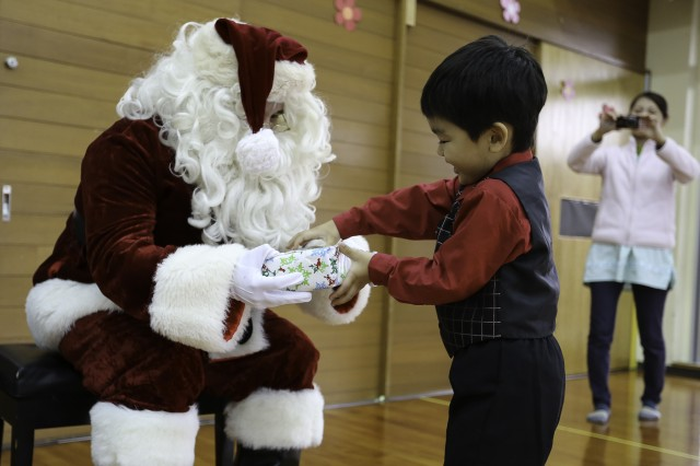 Santa hand a child a gift at the Tsukushi-En special needs school in Okinawa City Dec. 17.